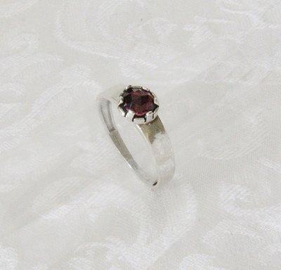 Handgemaakte ring van iets gehamerd zilver met een garnet steen.