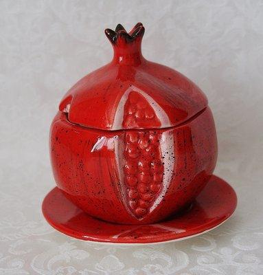 Honingpotje van aardewerk in de vorm van een granaatappel met schoteltje.