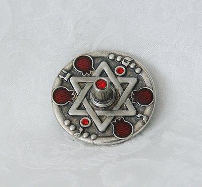 Handgemaakte dreidel van Yealat Chen met een Davidster en kleine granaatappeltjes in antiek zilverkleur rode steentjes