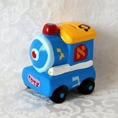Tzedakah (liefdadigheids) spaarpotje van aardewerk in de vorm van een geinig locomotiefje met Alef Beth decoratie. Ook leuk als gewoon spaarpotje voor kinderen