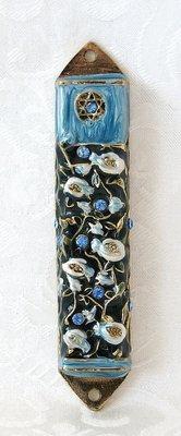 Mezuzah van opengewerkt koperkleurig metaal met een emaille decoratie van granaatappels en een Davidster