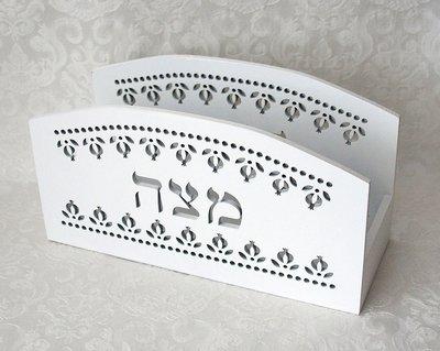 Matze standaard van wit hout met decoratieve uitsnijdingen van granaatappeltjes en het Hebreeuwse woord Matzah