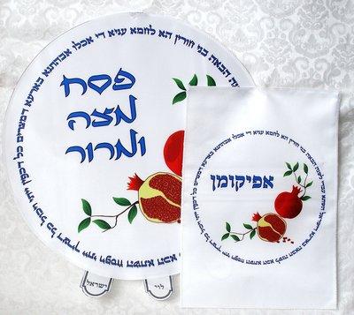 Pesach set van wit satijn met kleurrijke print van granaatappels en Hebreeuwse teksten die met Pesach te maken hebben.