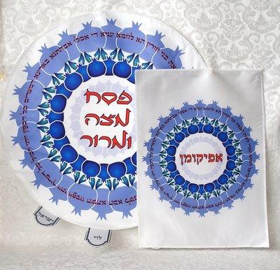Pesach set van wit satijn met rood/blauwe print van granaatappels en Hebreeuwse teksten die met Pesach te maken hebben.