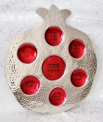 Seder schaal Granaatappel van gehamerd metaal met rode emaille, de namen van gerechtjes staan in het Hebreeuws en Engels vermeld