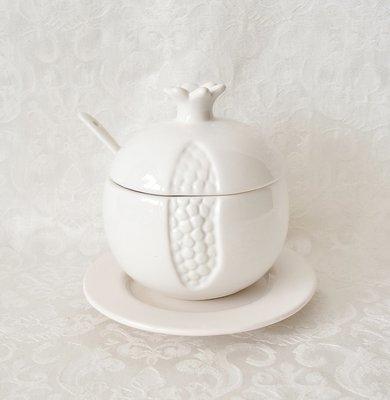 Honingpotje van wit aardewerk in de vorm van een granaatappel met schoteltje en lepel