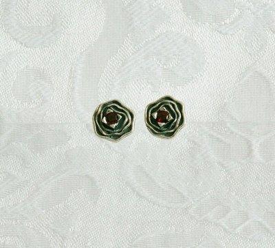 Oorknopjes, van zilver in de vorm van een kleine bloem met in het hart een donkerrood garnet steentje. Uit de Tamir Zuman collectie uit Israël.