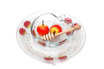 Honingschaaltje op schotel van versterkt glas met honingspateltje, feestelijk gedecoreerd met appeltjes
