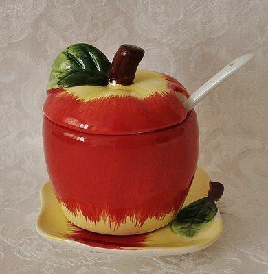 Honingpotje van aardewerk in de vorm van een appel met schoteltje in vrolijke kleuren.