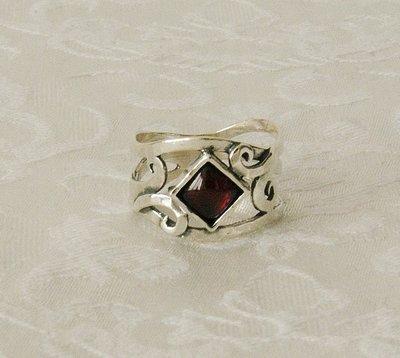Sierlijk gevormde zilveren ring, handgemaakt met vierkant garnetsteentje. Een bijzonder ontwerp van Tamir Zuman uit Israël