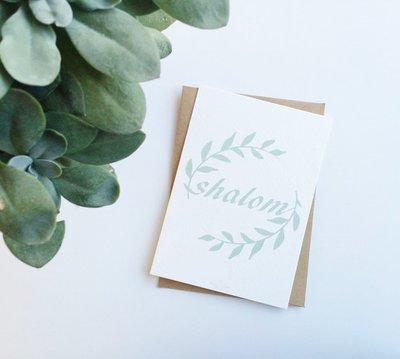 Kaart met envelop met Shalom (vrede) in gebroken wit met mintgroene letters en olijftakjes van Ahavah design