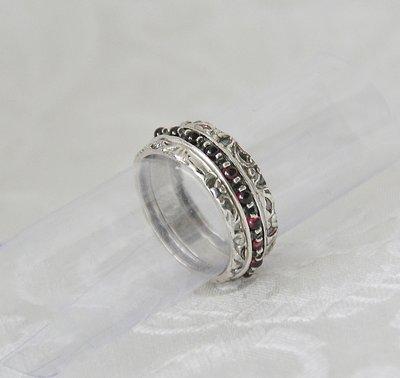 Handgemaakte zilveren stapelring set bestaande uit 3 afzonderlijke ringetjes. Een combinatie van 2 bewerkt zilveren ringetjes en 1 ringetje met rondom rode garnetsteentjes