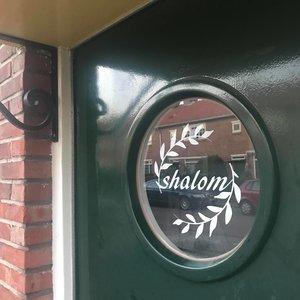 Shalom (=vrede) raamsticker gespiegeld, leesbaar vanaf de buitenkant raam