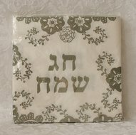 Papieren servetten met bloemdecoratie in zilver en de Hebreeuwse tekst: Chag Sameach (=Goede Feestdag)