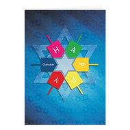 Chanukah kaart, langwerpige kaart met speels dessin van Davidster en Dreidels en de tekst: Happy Chanukah